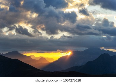 Red sunset in the mountains landscape with sunny beams. Dramatic scene of italian Dolomites with sun peaking behind a high mountains.