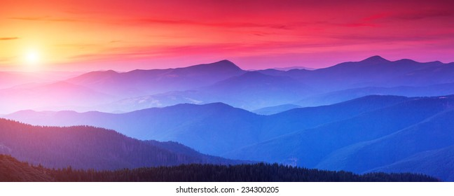 Red sunset in the mountains landscape with sunny beams. Dramatic scene. Carpathian, Ukraine, Europe. Beauty world. Retro style, vintage filter. Instagram toning effect.