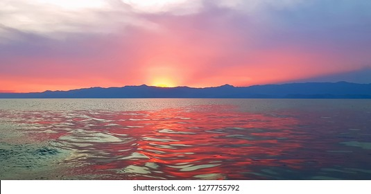 Red Sunset on Lake Kivu in Rwanda, East Africa. Glow of the sun dropping over the horizon in the evening with reflection on water and a dramatic landscape.
