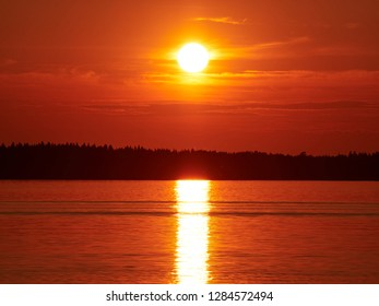Red sunset sky with the sun and colorful clouds above calm sea water in Vaasa, Finland. The bright disk of the sun is partly hidden by the clouds. Serenity consept.