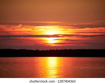 Red sunset sky with the sun and colorful clouds above a peaceful sea in  Vaasa, Finland. The bright disk of the sun is partly hidden by the clouds.