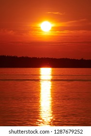 Red sunset sky with the sun and colorful clouds above calm sea water in Vaasa, Finland. The bright disk of the sun is partly hidden by the clouds. Serenity consept. Vertical image.