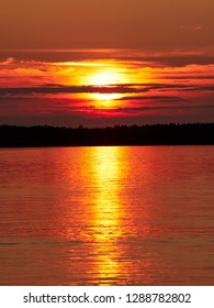 Red sunset sky with the sun and colorful clouds above calm sea water in Vaasa, Finland. The bright disk of the sun is partly hidden by the clouds. Very dramatic sky. Vertical image.