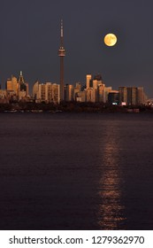 Red supermoon reflected in Lake Ontario rising over Toronto cityscape Toronto, Ontario, Canada - November 13, 2016