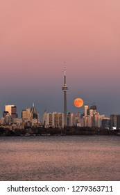 Red supermoon rising over downtown Toronto on November 13 2016 with pink sky and water Toronto, Ontario, Canada - November 13, 2016