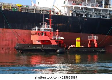 Red support tug and big cargo ship. Burgas port, Bulgaria