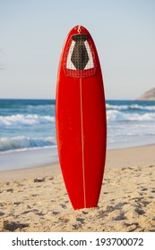 Red surfboard on the sand on a very beautiful sunny day
