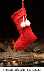 Red sweater knit Christmas stocking hanging in front of fireplace