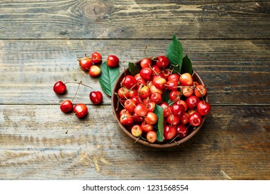 Red sweet sweet cherries in a plate on a wooden background. view from above. space for text