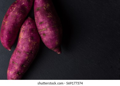Red sweet potatoes on slate