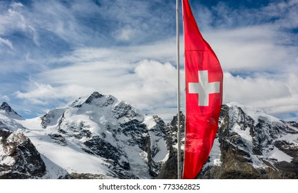 Red Swiss flag  at Swiss Alps over mountains  and clouds.