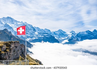 Red Swiss flag at Mannilichen top station  over mountains and above the clouds.