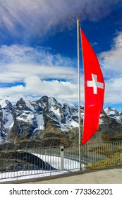 Red Swiss flag  over  Swiss Alps   and clouds.