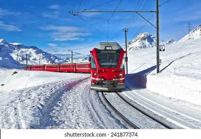 A red swiss train running through the snow, Switzerland