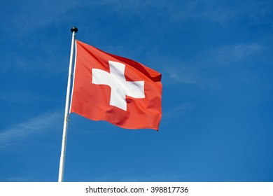 Red Switzerland national flag on pole waving against clear blue sky