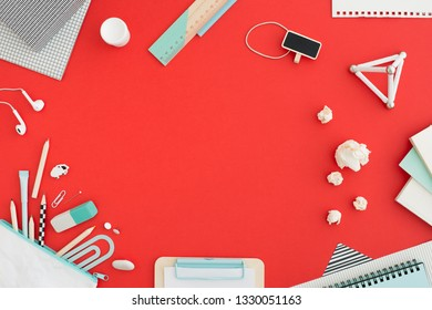 Red table and school supplies. Creative workspace. Flat lay.