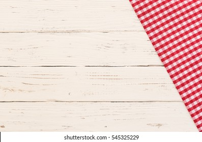 Red tablecloth on white wooden table background, top view, copy space.