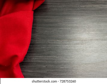 Red tablecloth on wooden table for background. Fabric texture. Wooden texture.Space for text. Top view. Template design