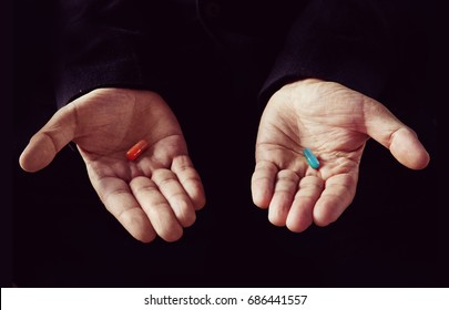 Red tablet in the left palm blue pill in his right hand