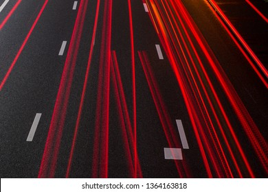 Red taillight stipes on the lanes of the Amsterdam A2 highway in the Netherlands.