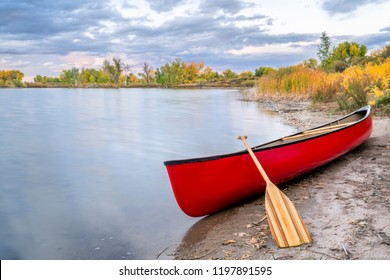 red tandem canoe with a wooden paddle on a lake shore, fall scenery