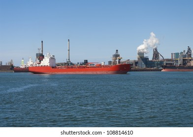 red tanker passing by a large steel factory in IJmuiden, Netherlands