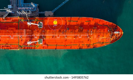 Red tanker ship loading and unloading oil and gas at industrial port, Business import export petrochemical oil and gas by tanker ship transportation.