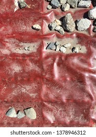 Red tarp with rocks on it being pressed into a grate.