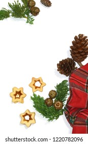 Red tartan plaid, Christmas cookies, pine cones and fir branches top view. Christmas composition elements on white table background, flat view minimalist image.