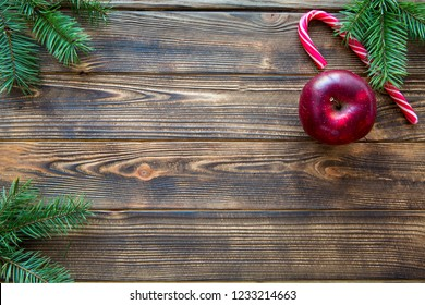 Red tasty apple and Christmas candy stick on brown wooden table background. Fir tree branches on the corners. Space for text. Copy space.