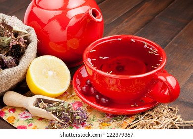 red tea cup and teapot, healing herbs and lemon on kitchen table