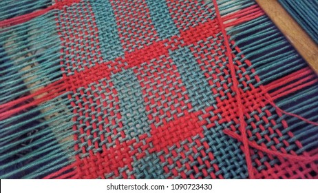 Red and Teal Yarn Partly Woven  on a Rigid Heddle Loom