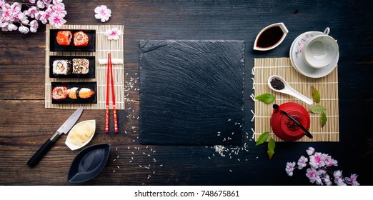 Red teapot, green leaves, slate tray and red chopsticks on old wooden table, Sushi rolls, nigiri, raw salmon steak, rice, cream cheese, avocado, lime, pickled ginger, asian background, top view
