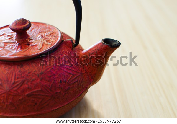 Red teapot on bamboo counter