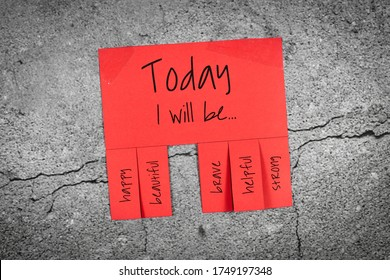 Red tear-off stub note with text 'Today I will be...' and words 'happy, beautiful, brave, helpful' and 'strong' on concrete wall background
