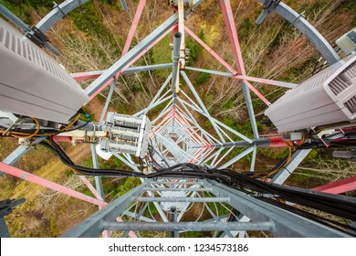 Red telecommunication tower or mast with microwave, radio panel antennas, outdoor remote radio units, power cables, coaxial cables, optic fibers are on the top mast that located in forest . View from