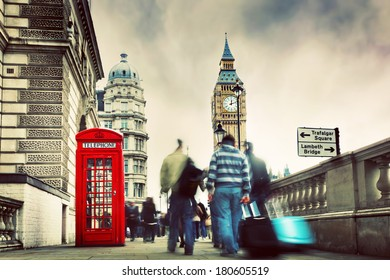 Red telephone booth and Big Ben in London, England, the UK. People walking in rush. The symbols of London in vintage, retro style
