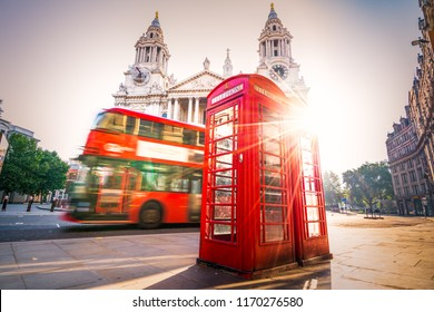 Red Telephone booth with sun flare and bus in motion near St Pauls Cathedral. London, Endland