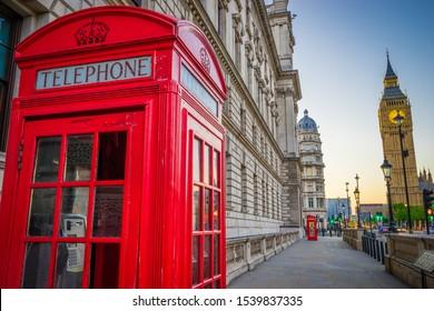 Red telephone both near Big Ben at sunrise. London, Great Britain