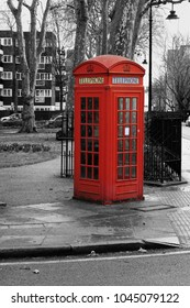 A red telephone box beside a a park with monochrome surroundings artistic view in Bloomsbury, London