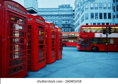 Red telephone box and bus in street with historical architecture in London.