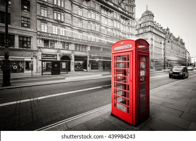 Red telephone box in street with historical architecture in London isolated.