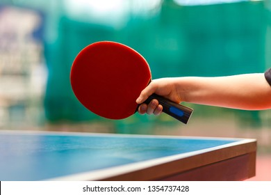 Red tennis racquet in the children's hand on a Dim background