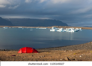 Red tent near Jokulsarlon glacier lagoon shore. Global warming and climate change concept with melting icebergs. Wild camping at the base of the Vatnajokull glacier at Jokulsarlon, Iceland.
