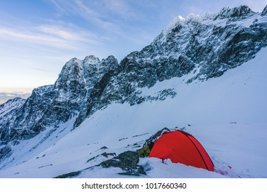 A red tent pitched up on snow in the middle of winter alpine landscape. Winter camping on snow. High alpine peaks, blue sky and bivi tent in winter alpine environment. Adventure and extreme alpinism