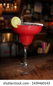 Red Tequila Margarita Frozen over a wood bar desk. Blurred background.