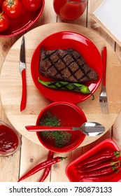 red theme lunch : fresh grilled bbq roast beef steak on red plate with green chili tomato soup ketchup sauce paprika small jug glass ground pepper american peppercorn and modern cutlery served wood