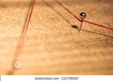 Red thread connects pins on cork board, soft focus
