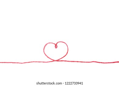 Red thread and heart isolated on white background