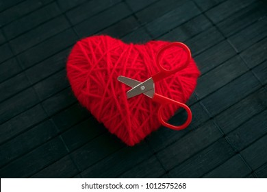 Red thread heart with red stuck scissors on black wooden  background. Handmade heart. Love, Jealousy, quarrel, divorce concept. Selective focus